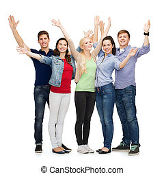 group of smiling students waving hands - education and...