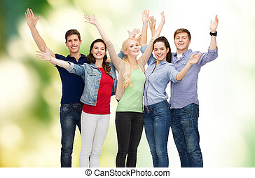 group of smiling students waving hands