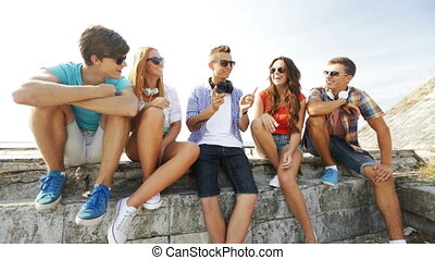 group of smiling teenagers hanging out outdoors - summer...