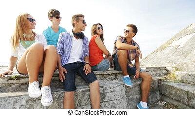 group of smiling teenagers making selfie outdoors