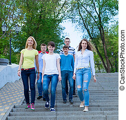 Group of smiling teenagers walking outdoors