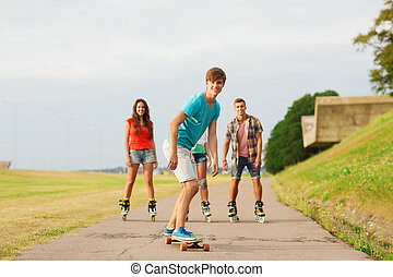 group of smiling teenagers with roller-skates - holidays,...