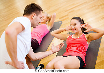 group of smiling women doing sit ups in the gym - fitness, ...