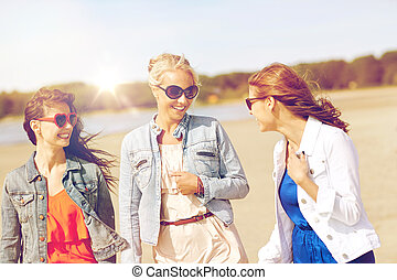 group of smiling women in sunglasses on beach