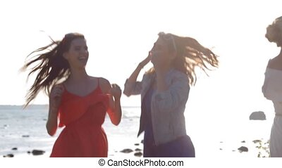 group of smiling women or girls dancing on beach 69