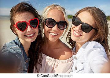 group of smiling women taking selfie on beach