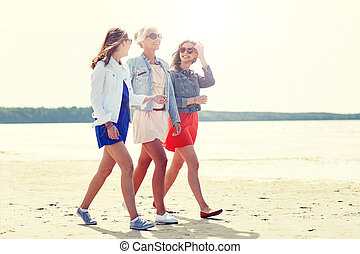 group of smiling young female friends on beach