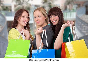 Group of smiling young women having fun in shopping mall