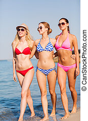 group of smiling young women on beach