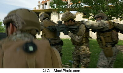 Group of soldiers with tactical maneuvers getting close to their objective in conflict area