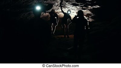 Group of speleologists explore the walls of the cave, close...