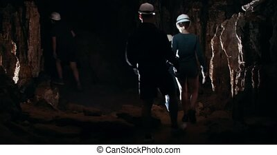 Group of speleologists going forward through the cave, close...