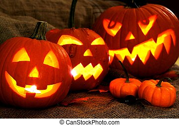Group of spooky Halloween Jack o Lanterns lit at night