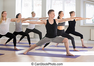 Group of sporty people practicing yoga, doing Warrior two pose
