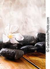 Group of black stones on wood base, steam background. Sauna, therapy, relaxation, and health concept. Vertical composition.