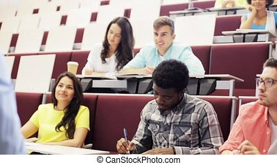 group of students and teacher in lecture hall - education,...