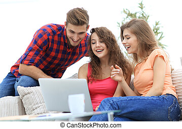 group of students looking at a laptop screen,sitting on the couch