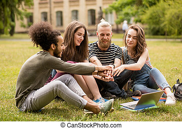 Group of students sitting on grass in University garden.