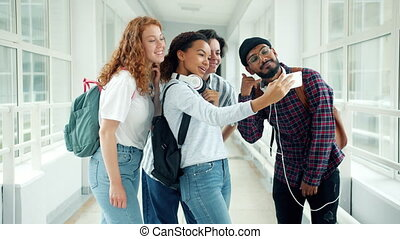Group of students taking selfie in university hall using ...