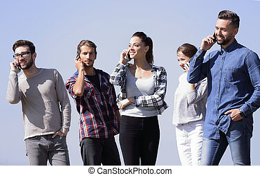 group of students talking on their smartphones. photo with ...