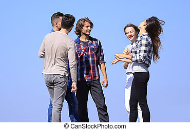 group of students talking while standing outdoors