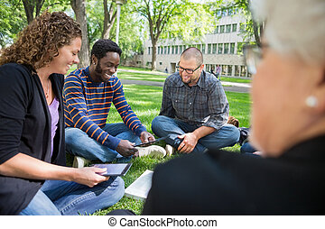 Group Of Students Using Digital Tablet On Campus
