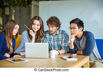 Group of students using laptop together