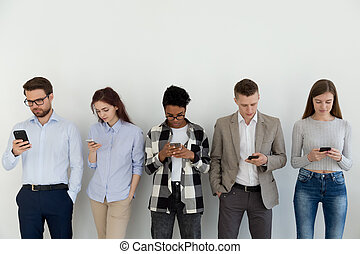 Group of students using smartphones standing indoors