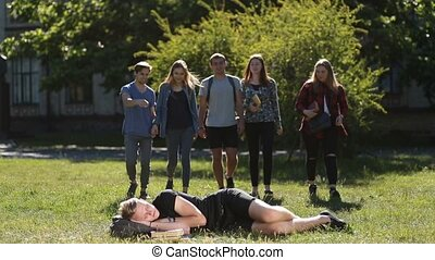 Group of students waking up sleepy friend in park