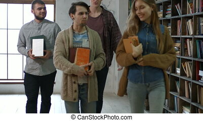 Group of students with books walking in library - Group of...