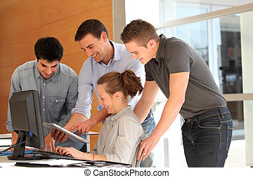 Group of students with teacher working on computer