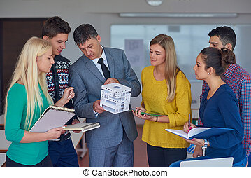 group of students working with teacher on  house model