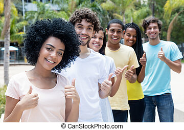 Group of successful multi ethnic young adults in line
