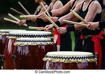 Taiko drummers drumming on Japanese Drums
