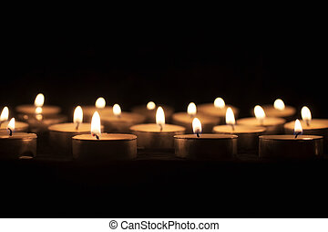 tea candles on a black background
