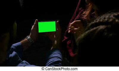 Group of teen laughing and having fun while watching a green screen smart phone