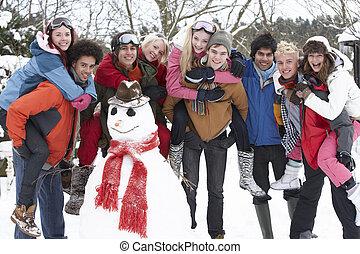 Group Of Teenage Friends Building Snowman In Garden