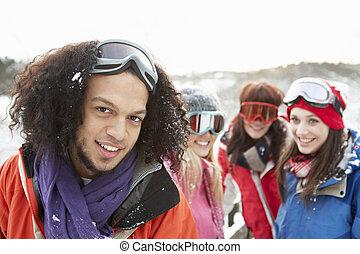 Group Of Teenage Friends Having Fun In Snowy Landscape Wearing Ski Clothing