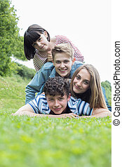 Group Of Teenage Friends Lying On Grass Together