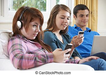 Group Of Teenage Friends Using Digital Technology At Home