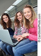 Group of teenage girls with laptop computer in school yard
