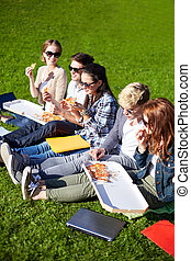 group of teenage students eating pizza on grass