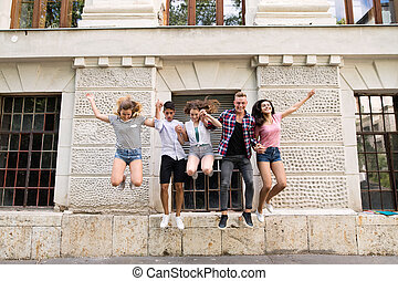 Group of teenage students in front of university jumping high.
