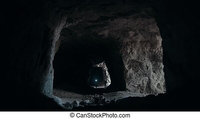 Group of teenagers comes into the dark cave with...
