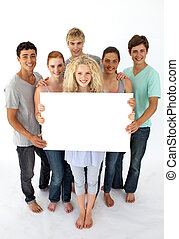 Group of teenagers holding a blank card agaisnt white...