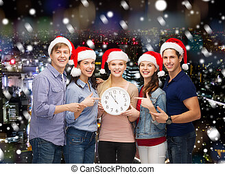 group of teenagers in santa helper hats with clock