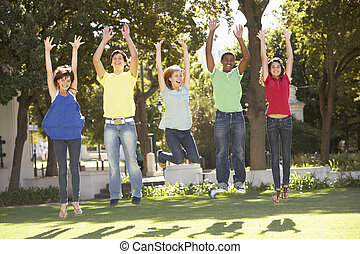 Group Of Teenagers Jumping In Air In Park
