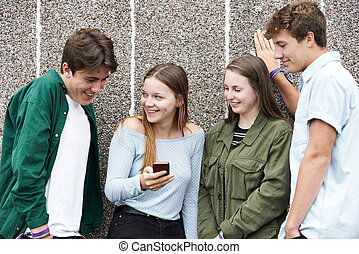 Group Of Teenagers Looking At Text Message On Mobile Phone
