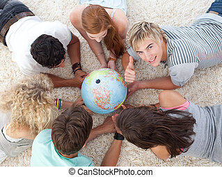 Group of teenagers lying on the floor examining a terrestrial world and a guy with thumb up