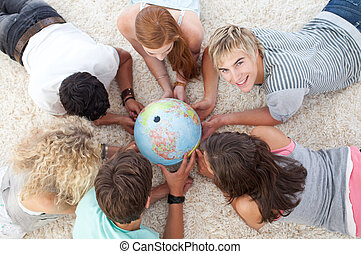 Group of teenagers on the floor examining a terrestrial world